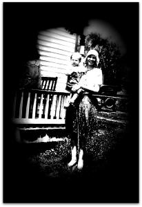 Ola Grimsley, my aunt, holding baby Ray at home of her parents, Tom and Florence Collier, in about 1930. Ruth Merica, my mother, is on the porch in background